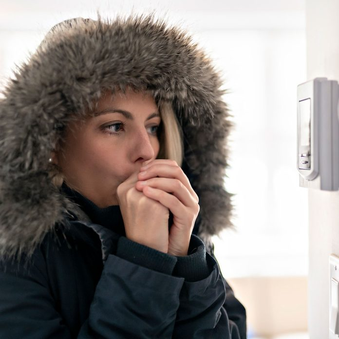 Woman wearing a winter jacket indoors, checking the thermostat