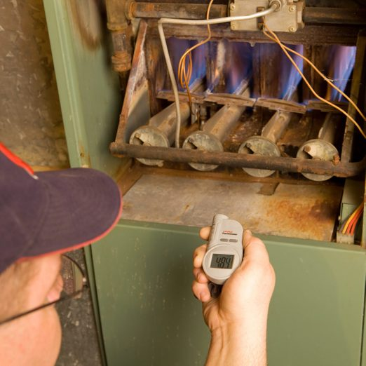 Repairman With Digital Infrared Thermometer Checks Gas Furnace Output Temperature