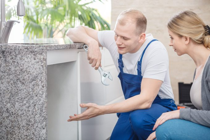 Plumber holding a wrench talking with a housewife about faucet damage