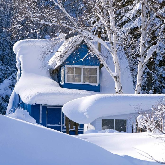 House with a large amount of snow on its roof
