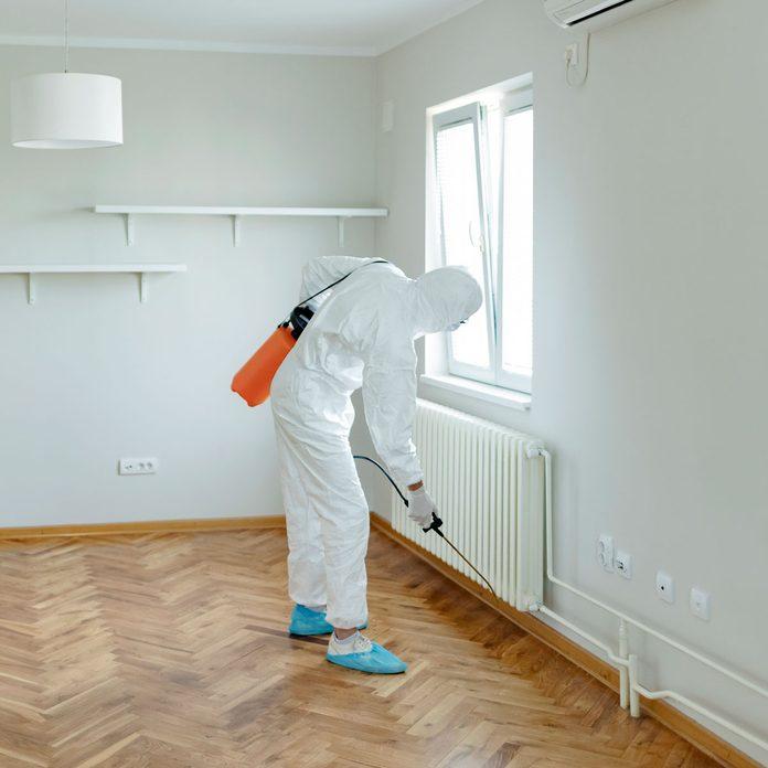 Exterminator spraying a home