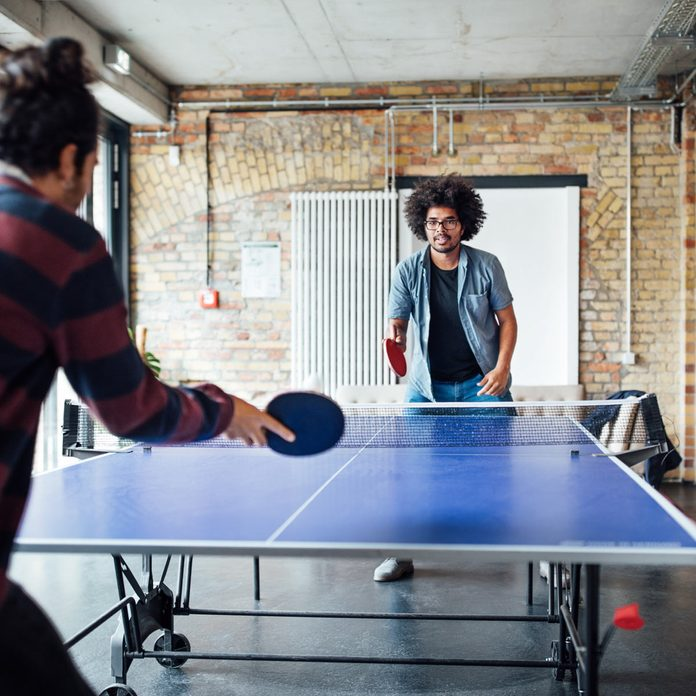 ping pong table playing table tennis with colleague Gettyimages 875610610