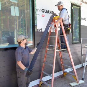 two workers siding a building