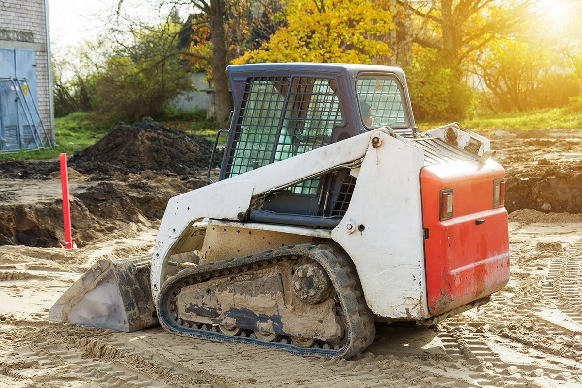 Mini excavator bobcat standing at construction site