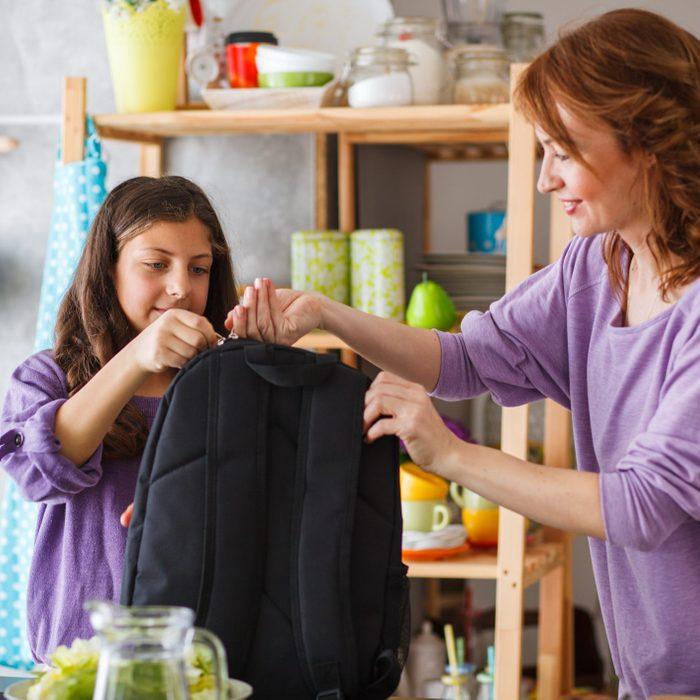 Mother and daughter packing backpack for school