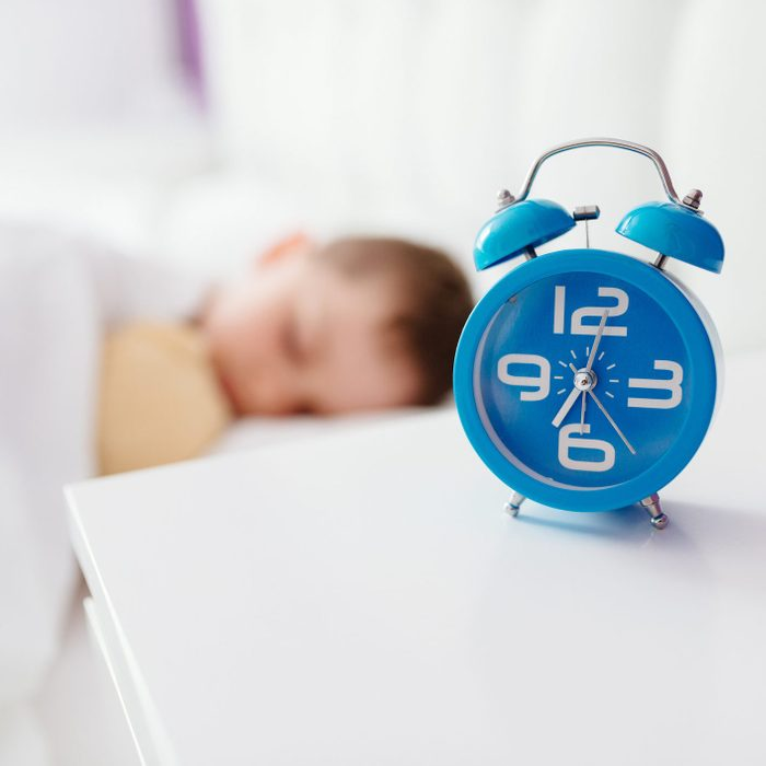 alarm clock on table next to young boy sleeping