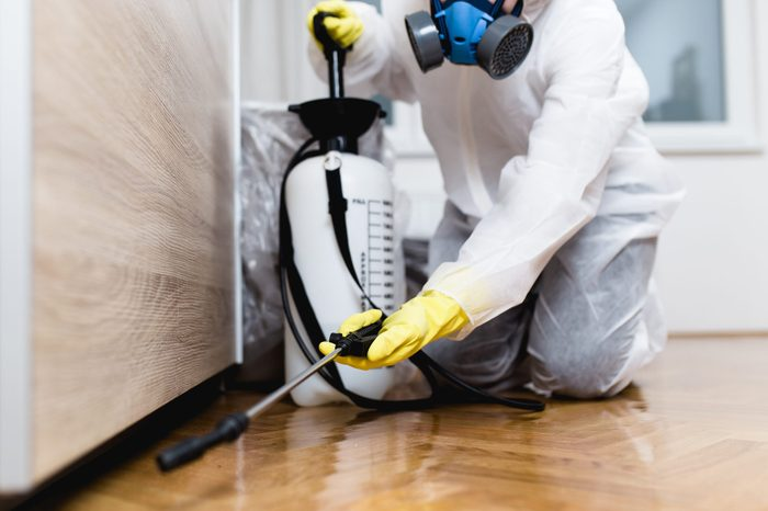 exterminator in protective gear spraying insecticide inside a home for cockroaches
