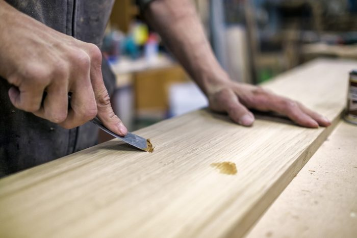 close up of man using wood filler or wood putty to fill holes in wood in his garage