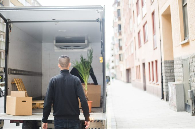 Rear view of man mover standing against truck on street in city