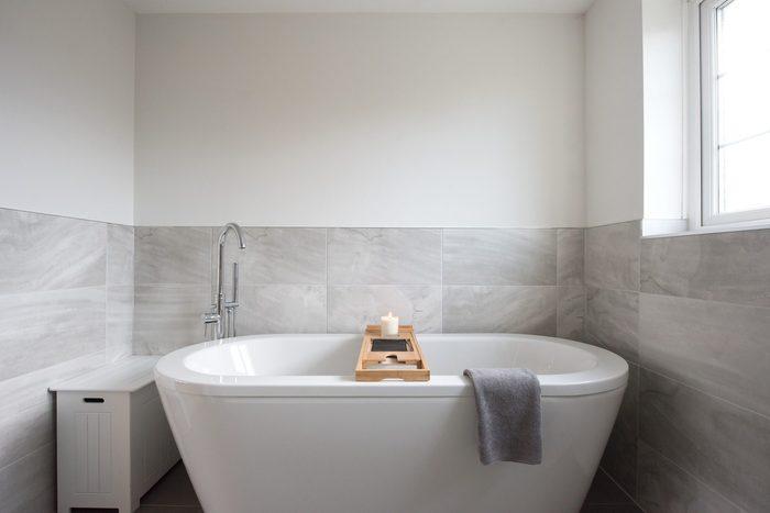 luxurious white bath tub in gray bathroom of home