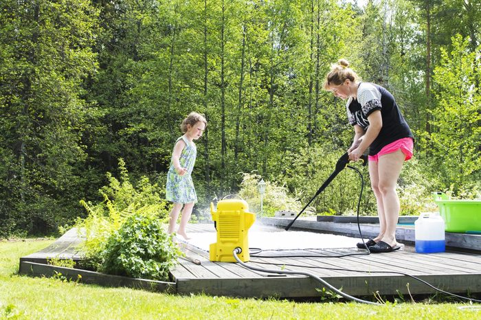 a woman with her child pressure washing an outdoor rug outside on the deck