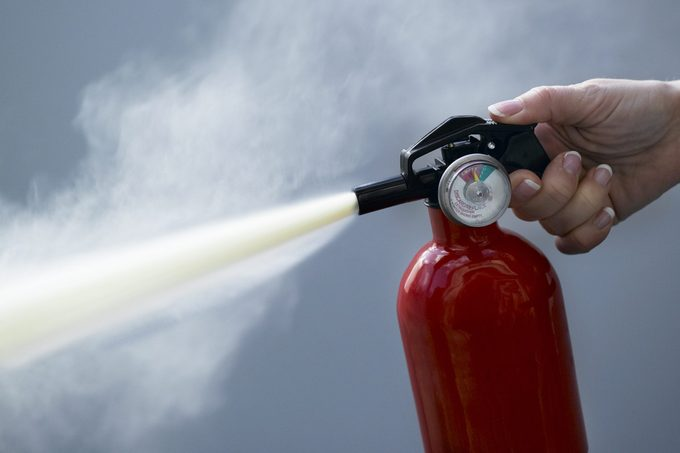 close up of person using fire extinguisher