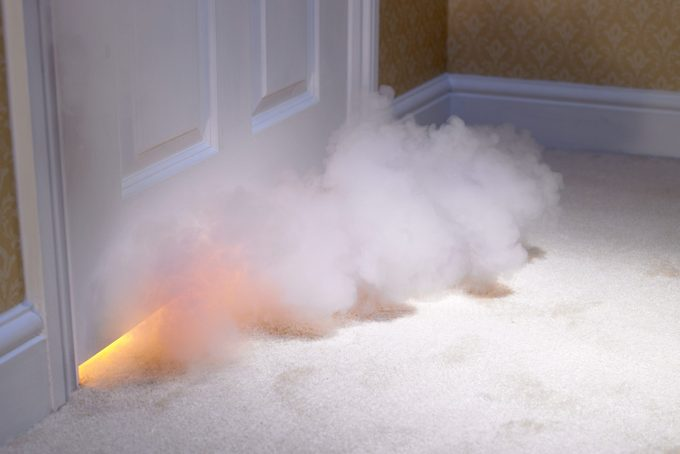 Smoke coming in under door from fire inside home