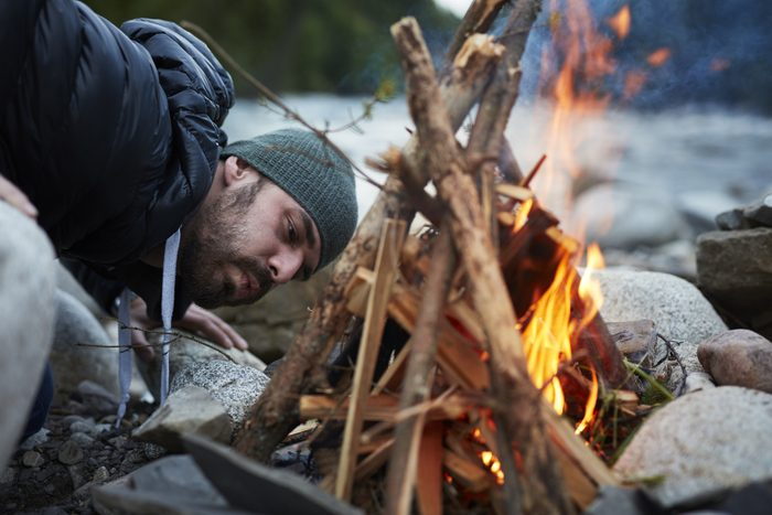young man starting a camp fire
