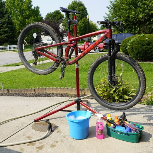 bike on a stand in the driveway with cleaning products surrounding it