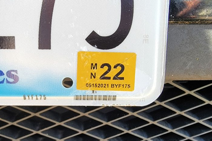 close up of License Plate Sticker With Score Marks